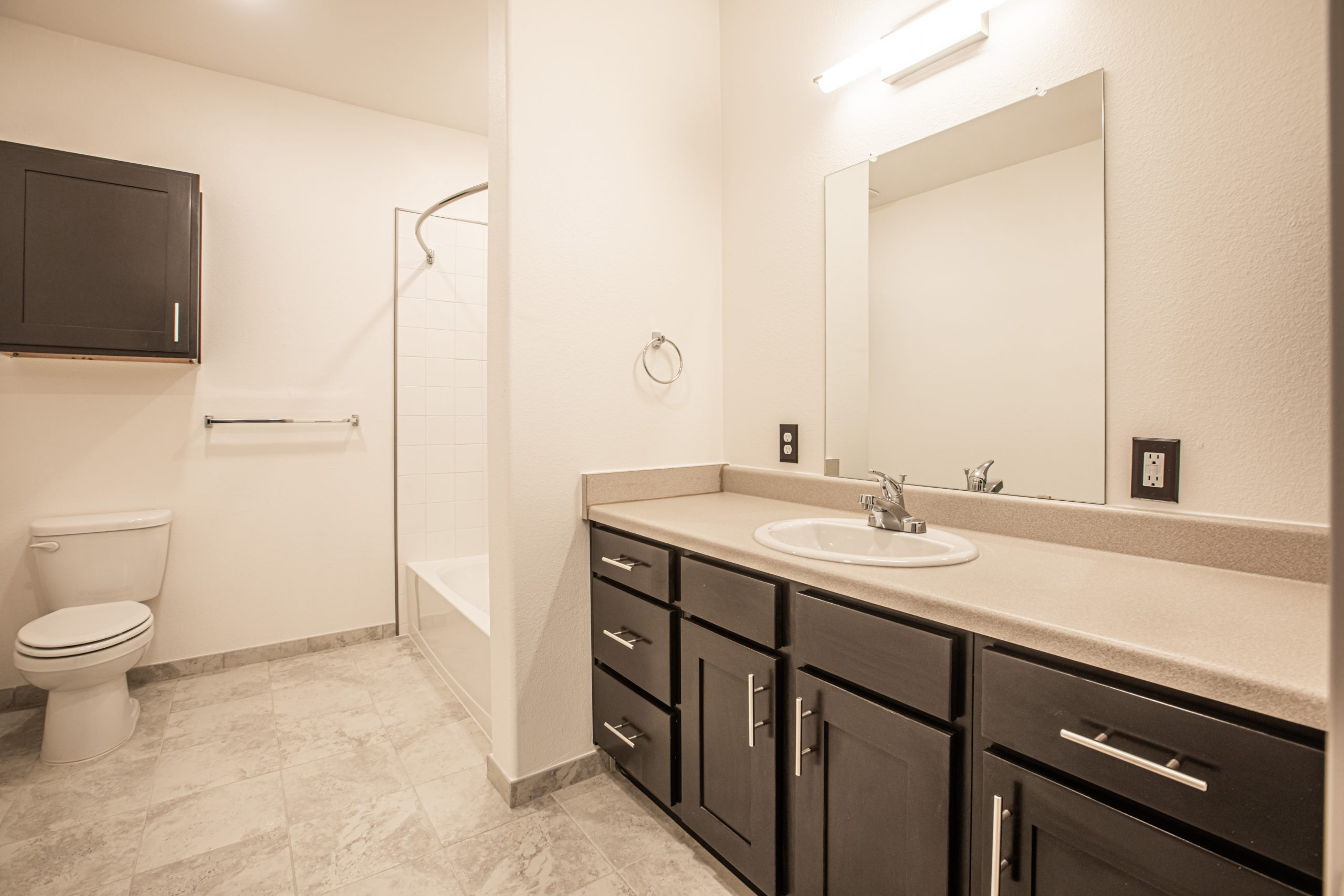 Apartment bathroom with sink, counter, toilet and shower